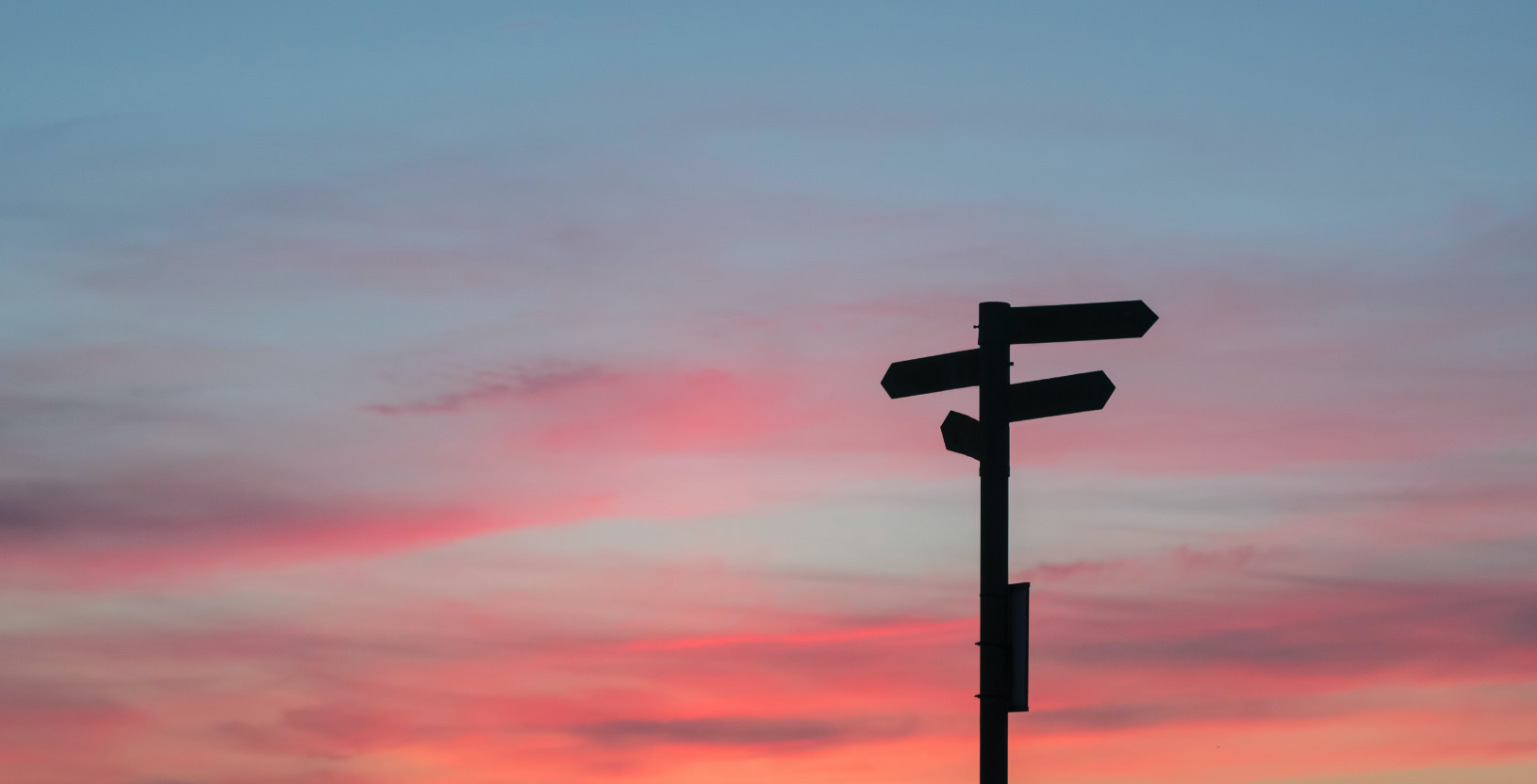 road sign silhouetted against the sunset sky