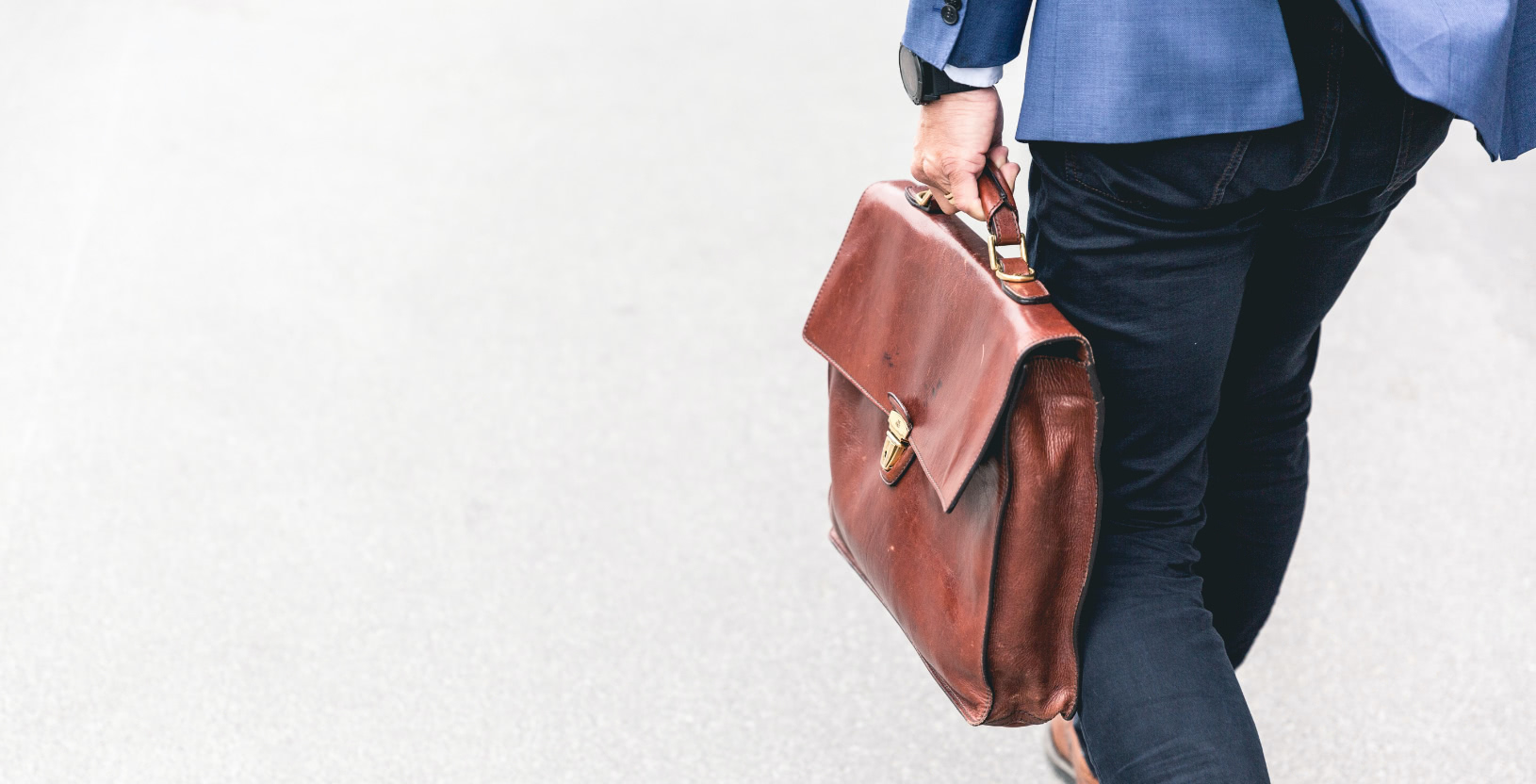 Insurance broker walking holding a brown leather bag