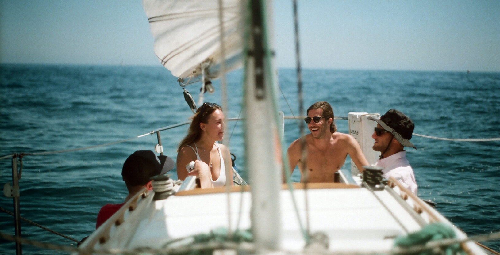 Four people sitting on a sailboat