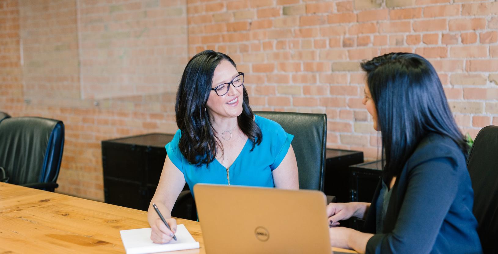Woman in teal t-shirt sitting beside an insurance broker