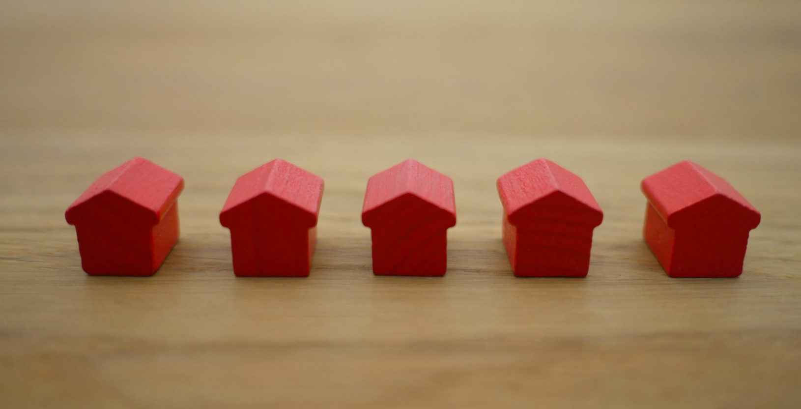 Five small red houses on a wooden table
