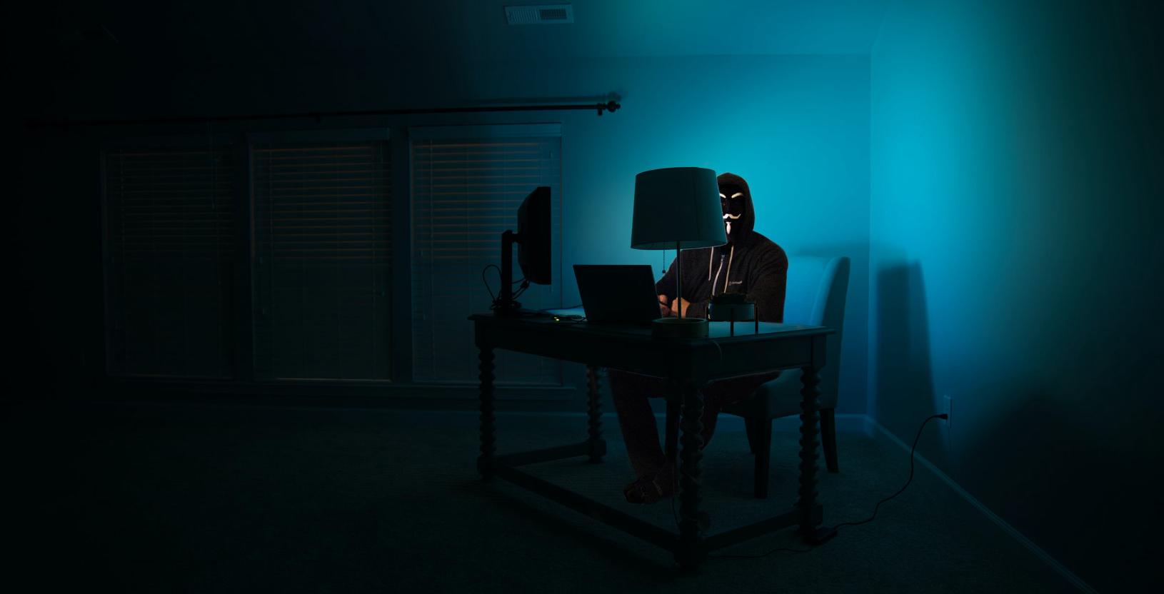 A hacker sitting at a desk in a dark room, facing a laptop